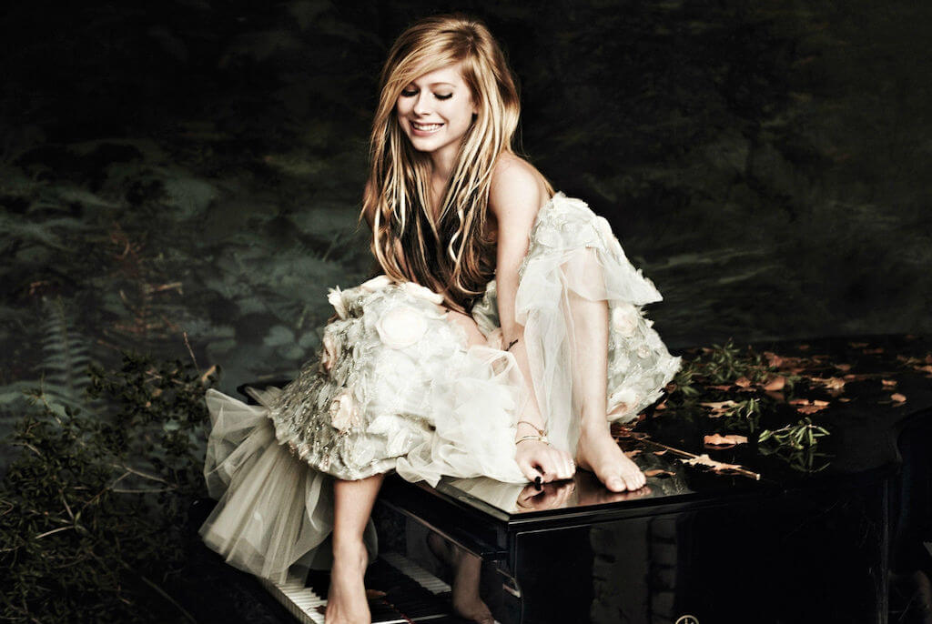 Avril Lavigne sitting on a piano