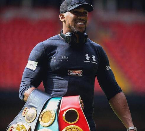 Anthony Joshua holding his belts