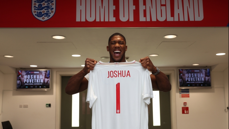 Anthony Joshua holding an England shirt